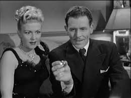 Criminals Bea (Christine McIntyre) and Dapper (Kenneth MacDonald) look at their loot – the stolen Punjab Diamond`