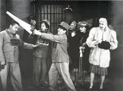 Publicity still for In the Sweet Pie and Pie, showing the Three Stooges (Moe, Larry, Curly) attempting to break out of prison while their wives watch