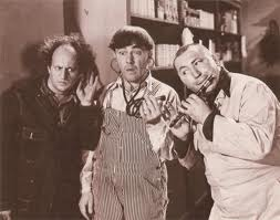 The Three Stooges (Moe, Larry, Curly) trying to coax a mouse in Termites of 1938